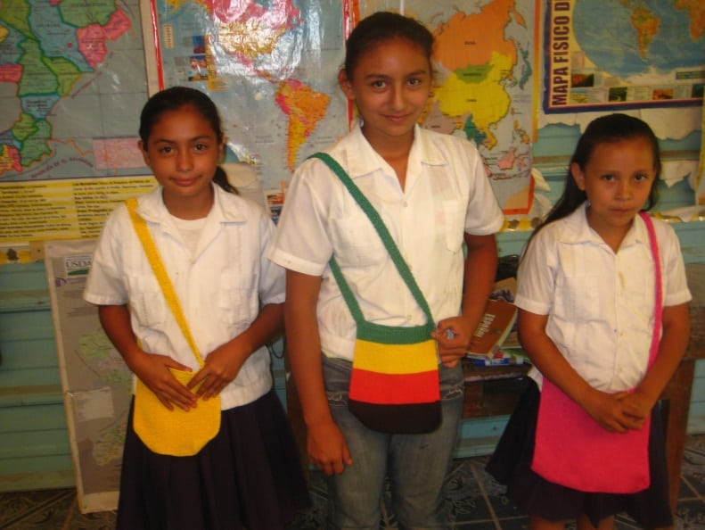 Three Yo Puedo participants proudly displaying their finished handbags they will sell for a small profit
